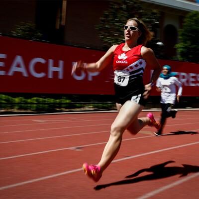 Female Canadian runner running on a track