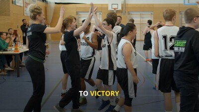 Two athletes giving a high-5 while the rest of the team surrounds them and cheers in victory