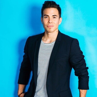 Apolo Ohno's standing in front of a light blue wall in a black jacket and white and black striped shirt