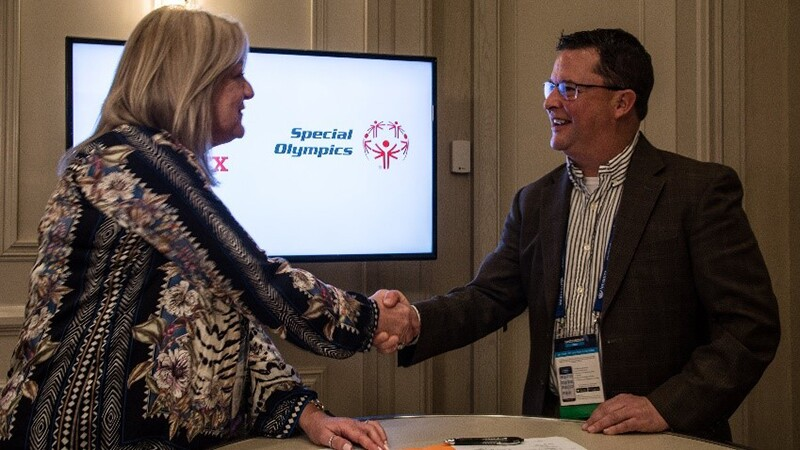 Man and woman shaking hands on stange in front of a Special Olympics presentation.