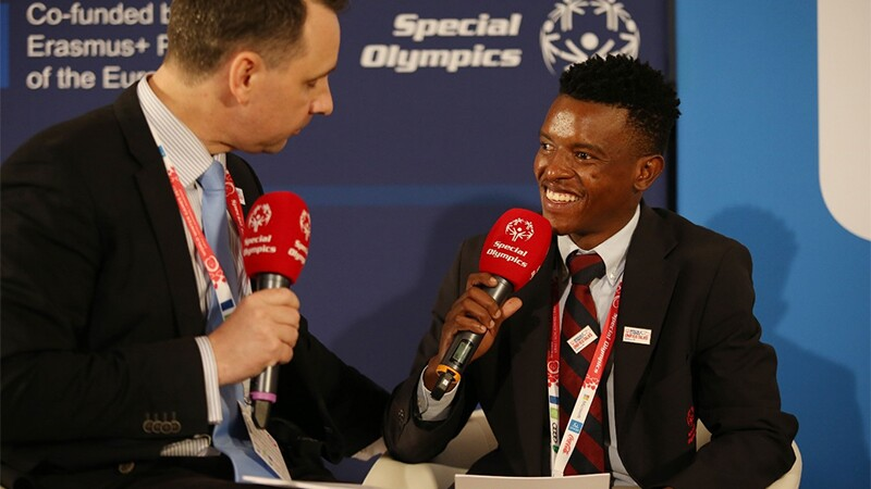 Two men speaking into microphones while sitting down facing each other.