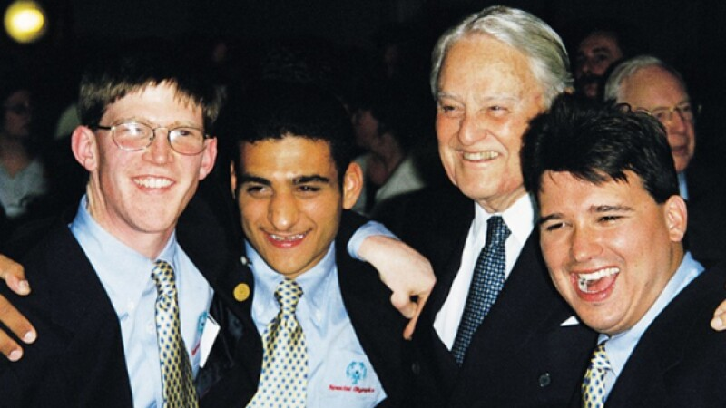 Thee young and one older man (Sargent Shriver) standing together smiling for a photo.