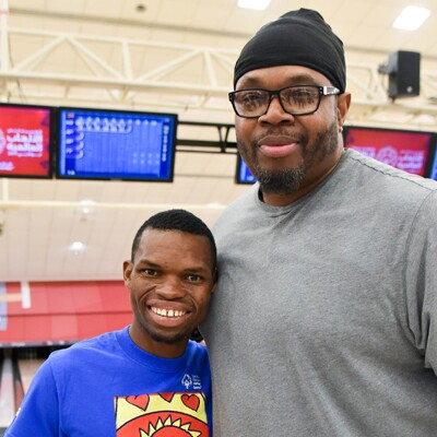 Sam Perkins standing with a young man in a bowling alley