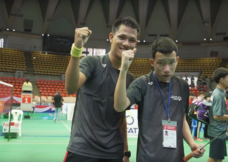 two badminton players raising their hands in victory.