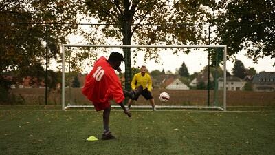 A man in a red football kit with his back to the camera kicks a football towards the net and a goalkeeper in yellow.