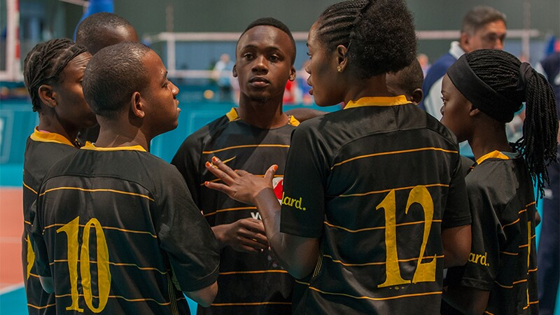 Tanzania Unified volleyball team in a huddle.