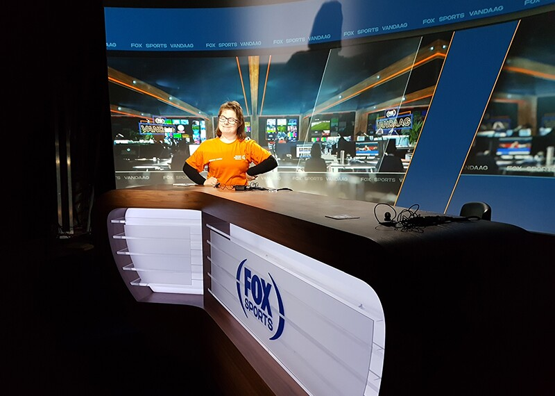 Lize sitting behind the FOX sports news desk with her hands on her hips and smiling.