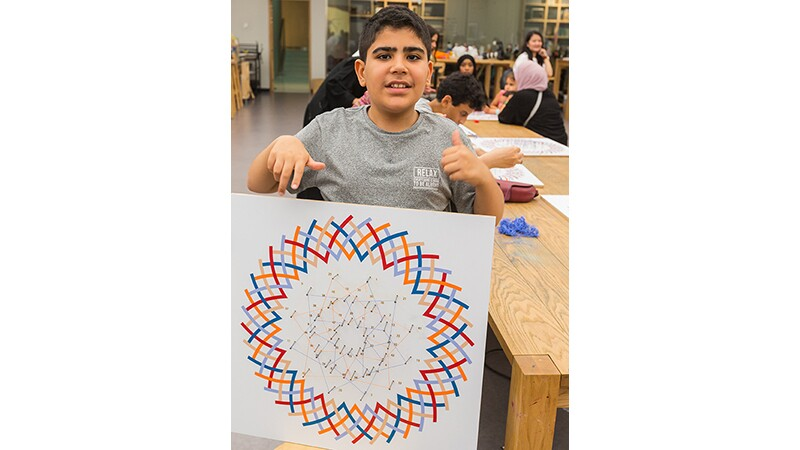 An unified art student shows off his completed artwork.