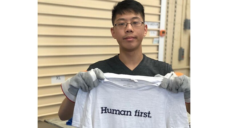 Jason, Spectrum employee, standing outside holding a shirt that says, Human first.