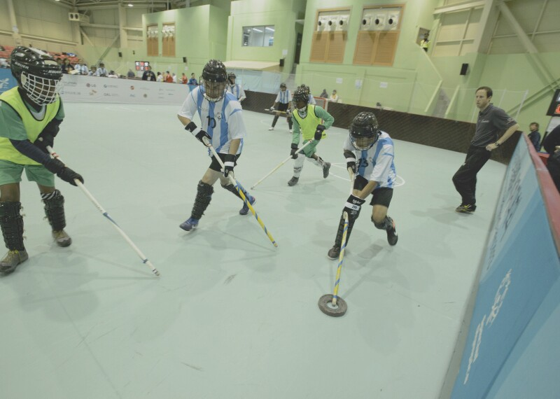 An athlete with the puck tries to make his way past a player for the opposing team.