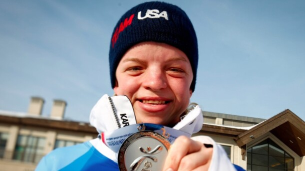 Daina Shilts holding up her silver medal at the 2013 Special Olympics.