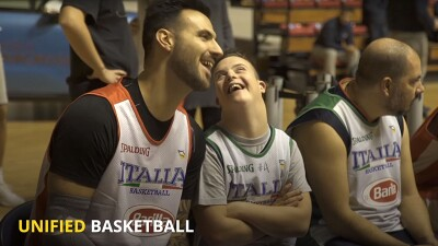 Unified athlete and Special Olympics athletes from Italy sitting on the side lines talking and sharing a laugh.