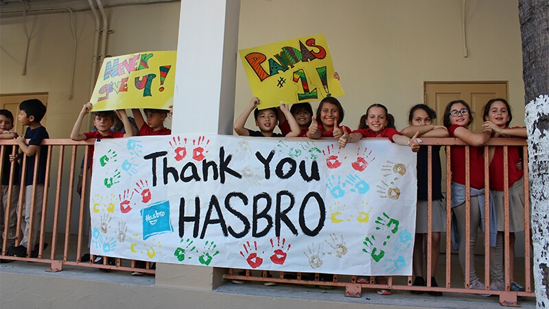 Young students standing behind a banister holding signing that reads, Thank you Hasbro.
