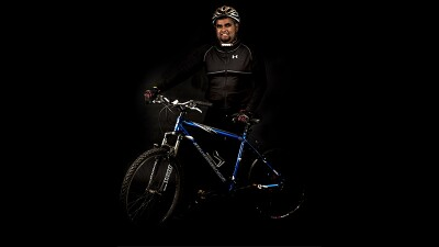 Al-Sayyed Curumthaullee standing in a black photography studio dressed in his black cycling gear standing next to a blue bicycle.
