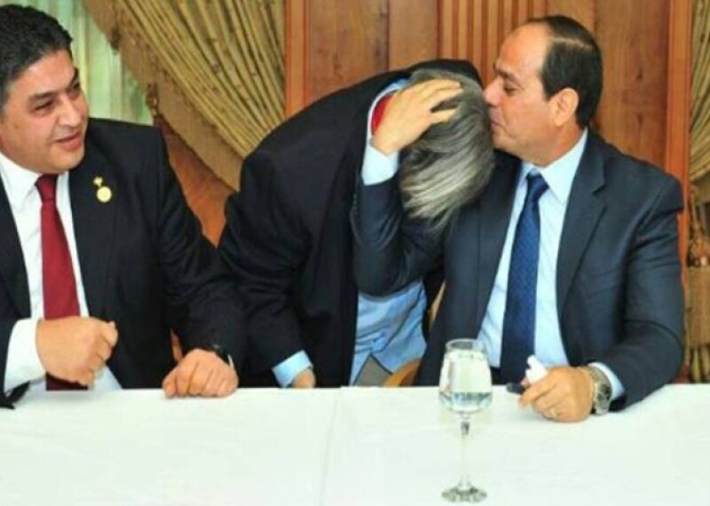 Dina Galal being embraced and kissed on the top of the head by Egyptian President Abdel Fattah El Sisi. President President Abdel Fattah El Sisi is seated at a dinner table wearing a blue suite, white shirt and blue tie. Also pictured is a seated man (to the left) smiling and wearing a black suite, white shirt and red tie with a gold pin on his left lapel.