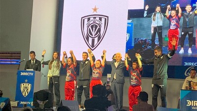 A group of athletes and Special Olympics representatives are on stage holding hands with their arms raised in victory.