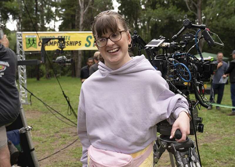 Actress and Special Olympics athlete Sarah Dalton standing next to a video camera on the set of Power Rangers Dino Fury.