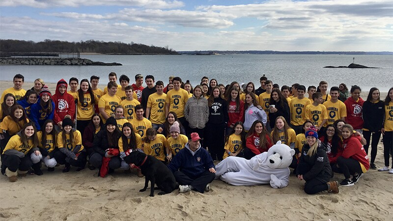 Group of participants, athletes, and representatives on the beach in a group photo.