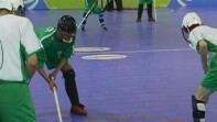 Athletes in the midst of a floor hockey game.