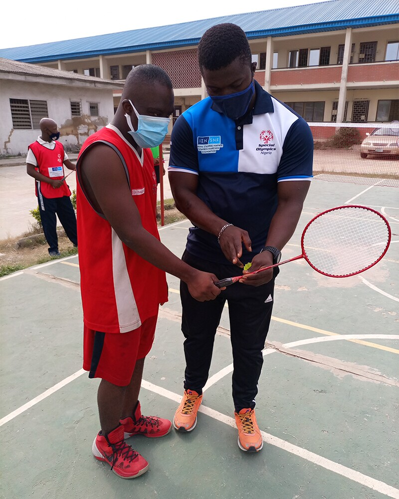 A coach and an athlete standing side by side on a badminton court while the coach points to a badminton racquet and shuttlecock.