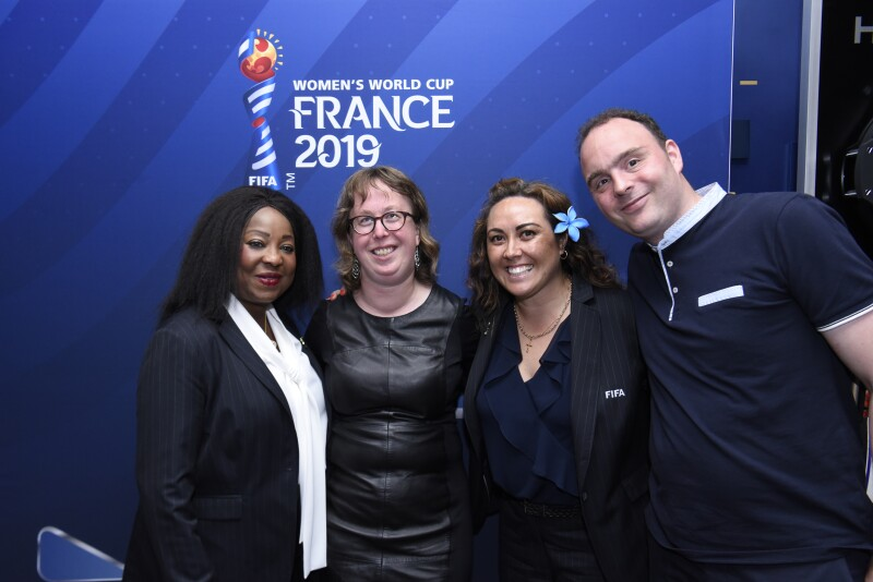Three women and one man face the camera smiling with blue FIFA Women's World Cup France 2019 branded wall in the background.