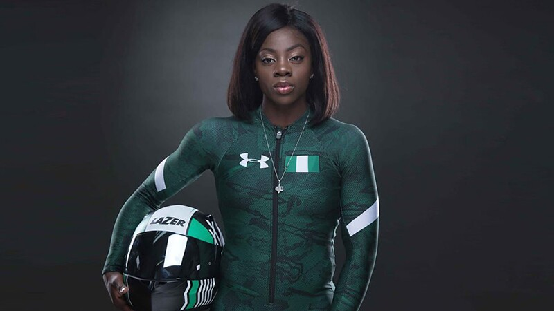 Professional photos of Seun Adigun. She is looking straight forward at the camera, has on Under Armour green and black suit; she is holding her Lazer helmet under her right arm.