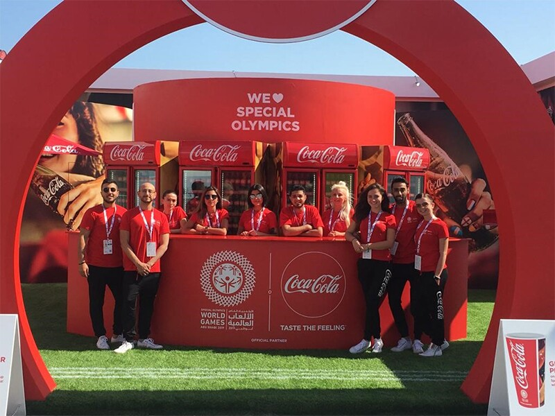 Coca Cola representatives standing at the Coca Cola booth in Abu Dhabi at the summer games.