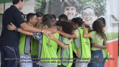 One adult and a group of young kids in a circle hugging one another wearing Special Olympics El Salvador neon jerseys.