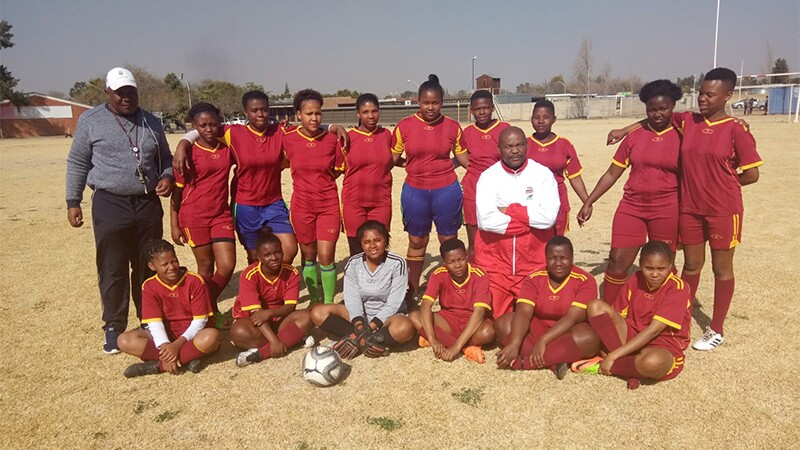 Moeti Clement Sethunya standing with his female football team on a filed for a group photo.