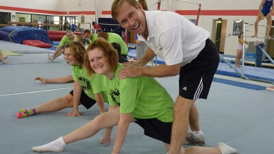 Bart Conner with gymnastics athletes in the gym.