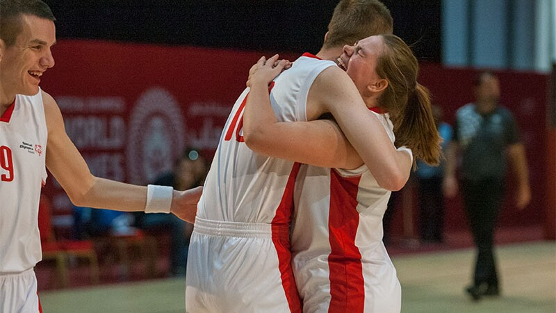 Male and female athlete hugging on the basketball court.