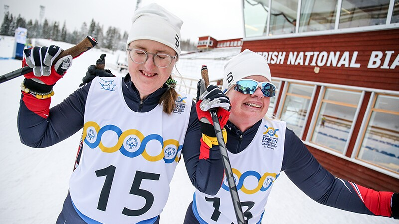 Two women both holding ski poles and smiling in celebration.