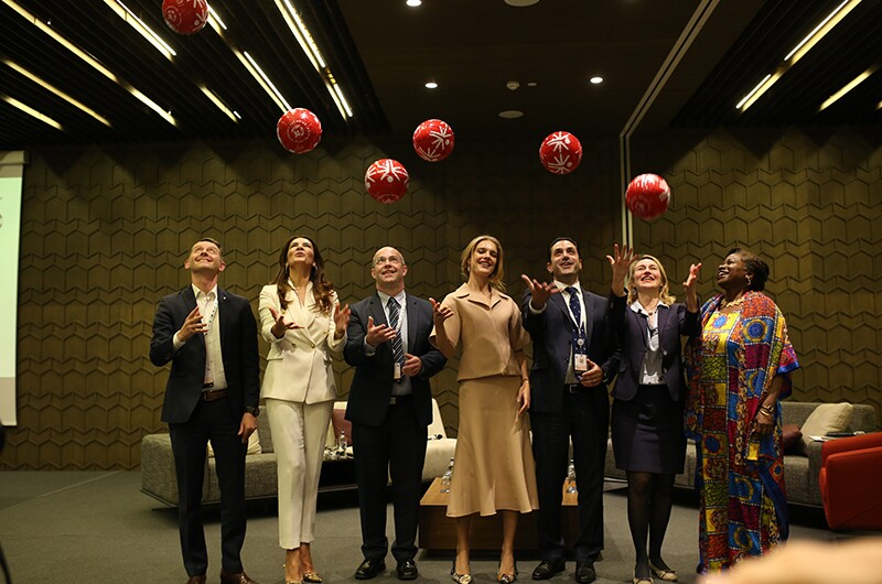 "Special Olympics Europe Eurasia President and Managing Director, David Evangelista, with Special Olympics International Board Member, Natalia Vodianova, and panel at 2018 ""Let's Talk"" event, hosted by Ms. Vodianova. Everyone tosses a Special Olympics footballs up in the air for a staged photo."