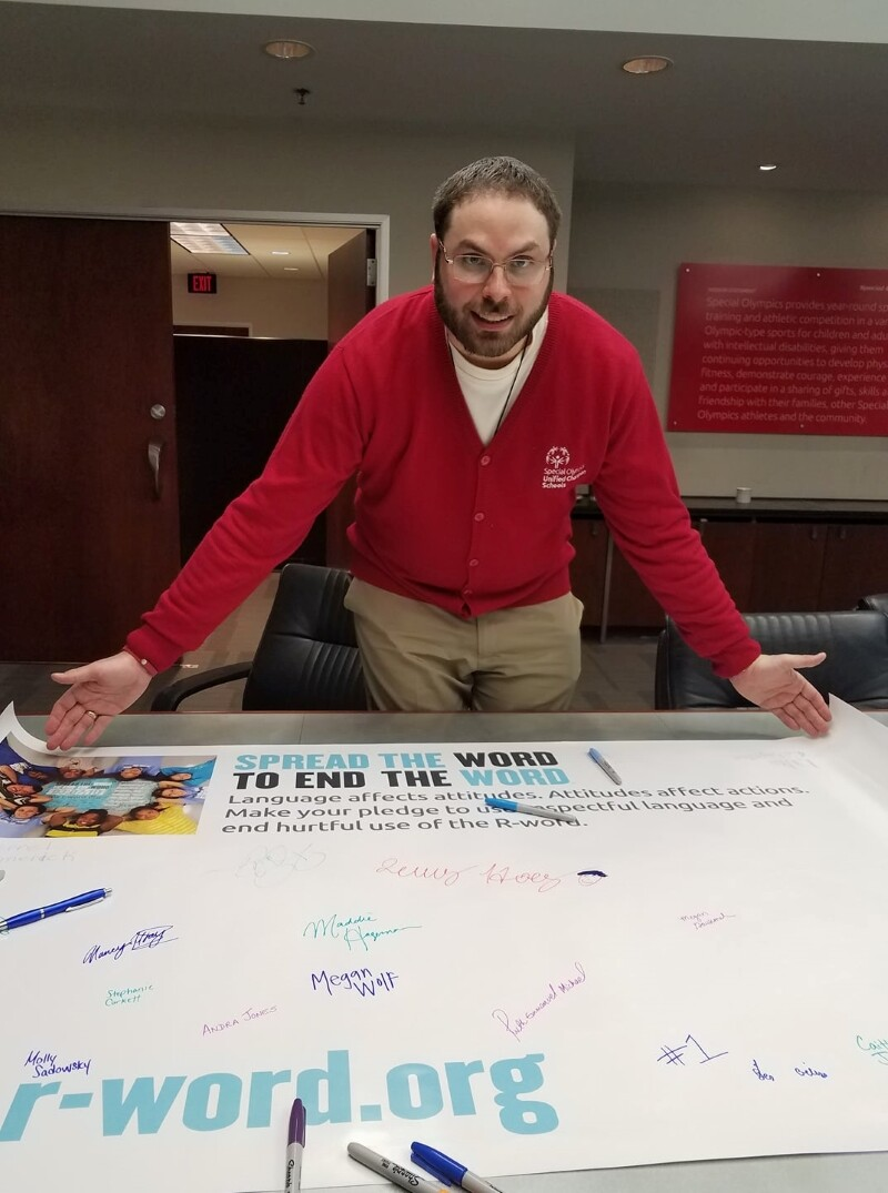 A Special Olympics athlete wearing a red sweater stands near a poster.