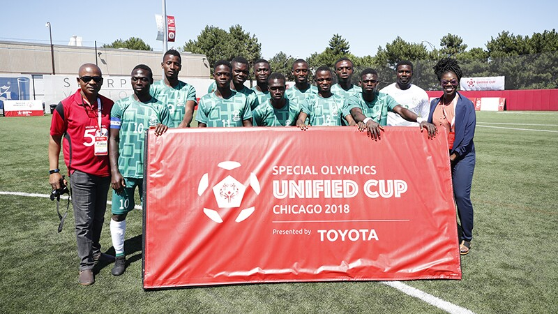 Seun with a unified team on a soccer field. The team is holding a large red banner that reads: Special Olympics Unified Cup, Chicago 2018 presented by Toyota.