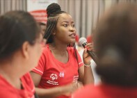 Young woman in a  red Special Olympics t-shirt holding a microphone and speaking to someone she is looking at off in the distance.