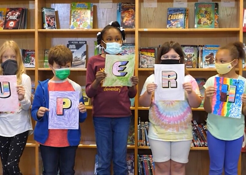 Children holding up signs with different letters colored in.