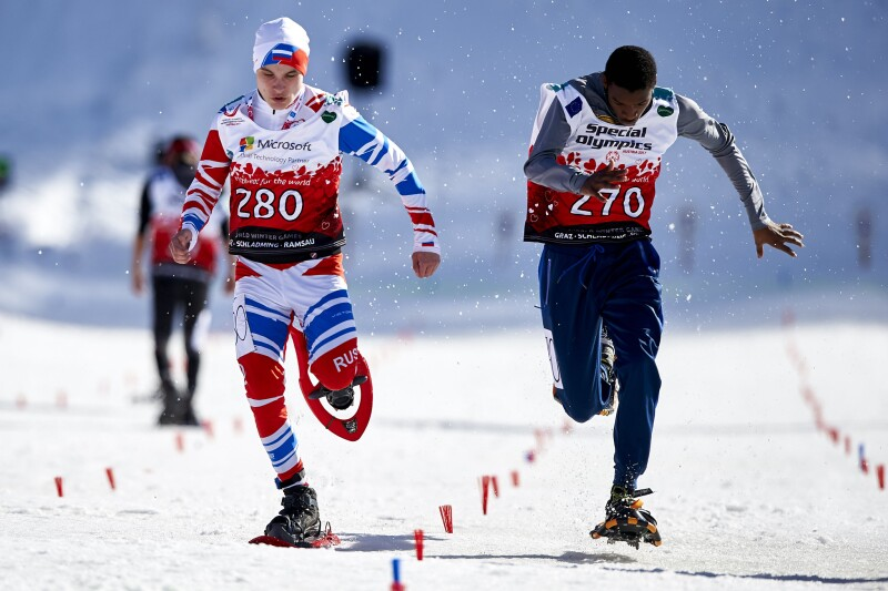 Two male athletes running on a snowy surface towards the camera in snowshoes.