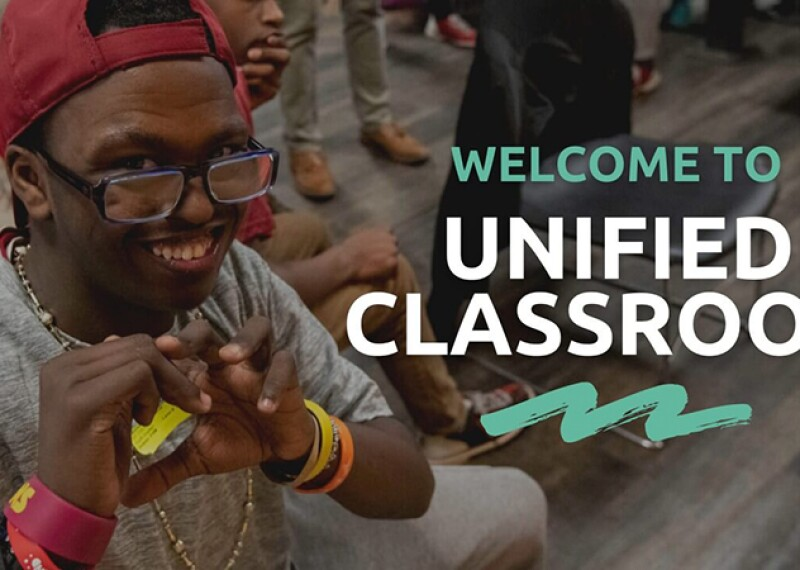 "A student smiles and makes a heart shape with his hand, with the words ""Welcome to Unified Classroom"" on the graphic."