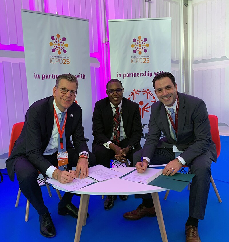 Three men sitting at a table; each man on either side of the middle man are signing papers. Signage in the background reads: ICPD25 in partnership with Special Olympics.