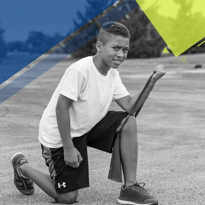 Young man kneeling down on the asphalt working out with a resistant band