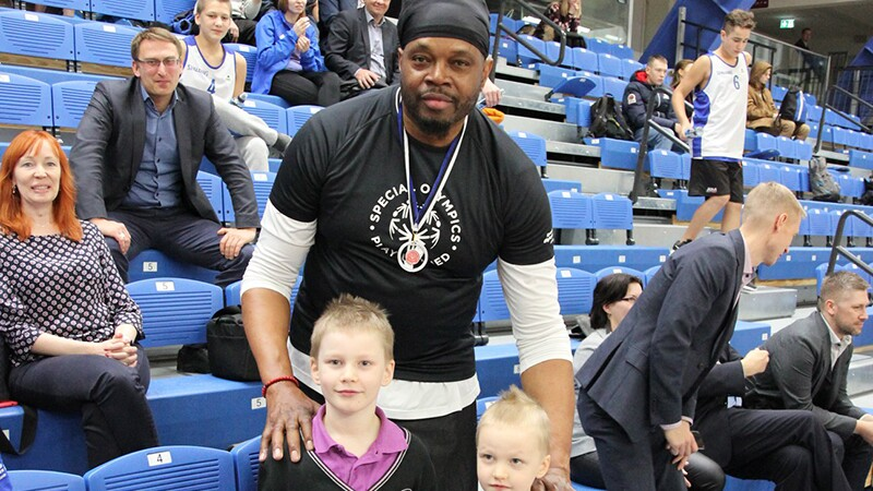 NBA legend, Sam Perkins stand behind two young fans for this photo. Sam has on a Special Olympic Play Unified black t-shirt.