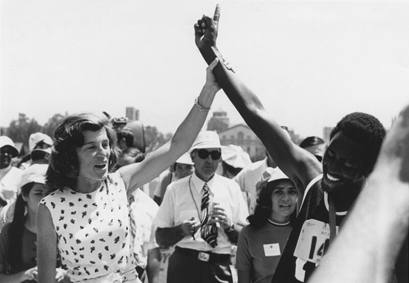 Eunice Kennedy Shriver holding an athletes arm up in victory.