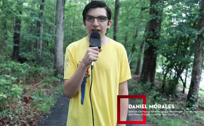 A Special Olympics athlete wearing a yellow Torch Run t-shirt is holding a microphone and speaking to the camera.
