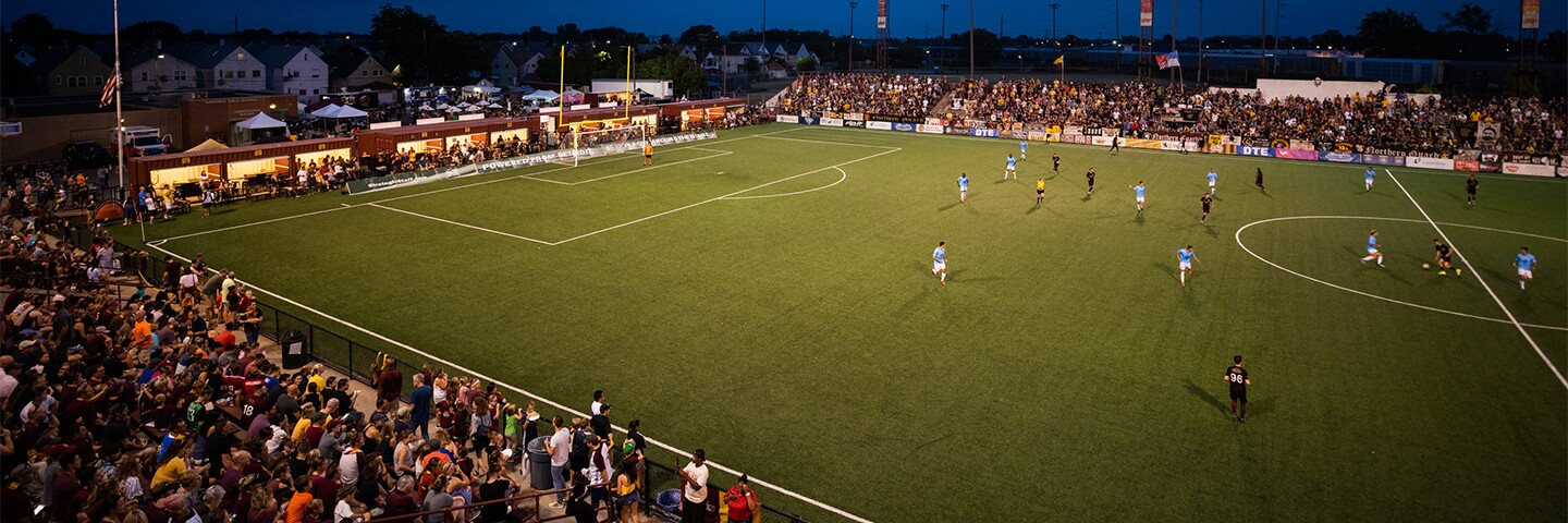Night football (soccer) game; spectators in the stands and a game on the field.