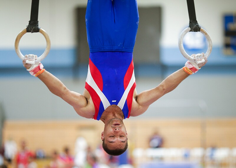 Man performing on the still rings; he is upside down holding an inverted cross pose.