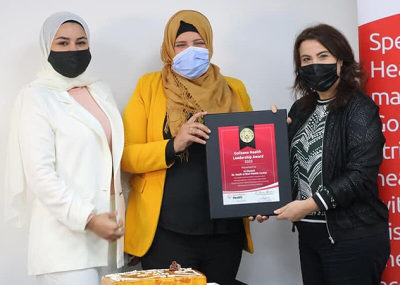 Two women receiving an award from another woman.