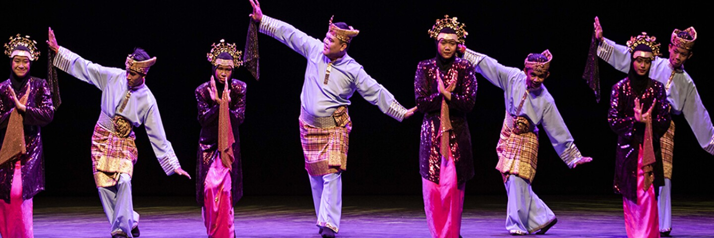 Dancers in costume on stage performing.