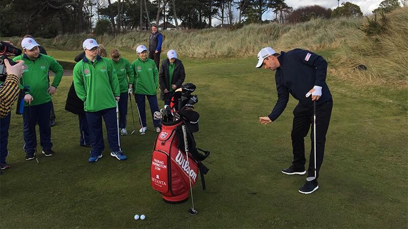 Golfers on the green watching Padraig Harrington at the hole.
