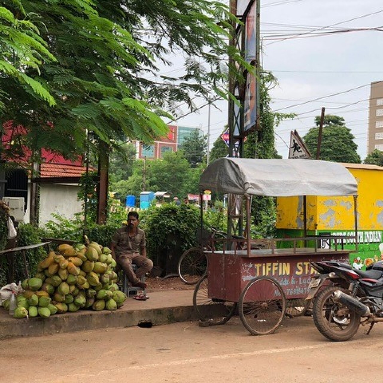 A man is sitting on a stool next to a stack of coconuts on a sidewalk. A cart and motorcycle sit in the street.